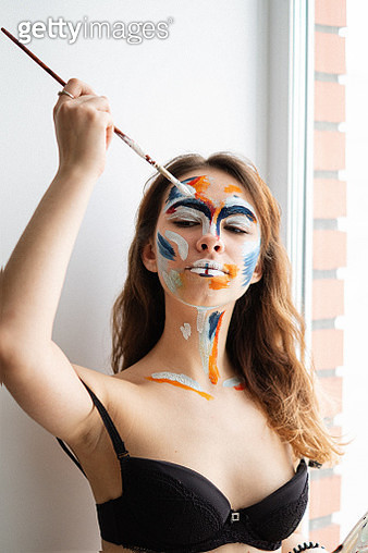 Woman Applying Paint On Face - gettyimageskorea