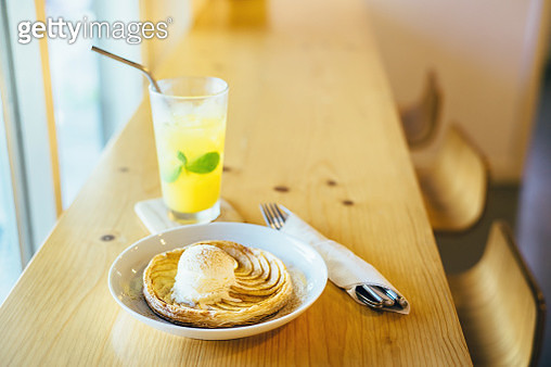 A glass of refreshing iced passion fruit and mango soda and apple pie with ice-cream freshly served on table in the cafe in a hot summer day - gettyimageskorea