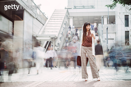 Pretty young lady using smartphone on busy street - gettyimageskorea