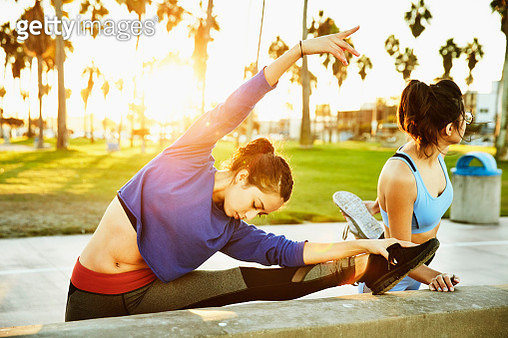 Woman stretching on wall before early morning run with friends - gettyimageskorea