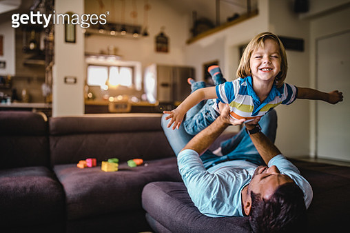 Joyful boy having fun while playing with his father at home. - gettyimageskorea
