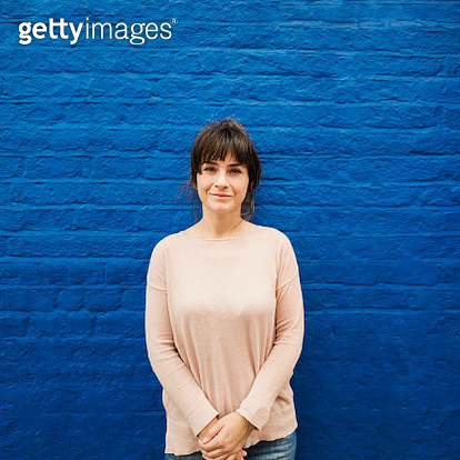 Portrait of a smiling woman standing by a blue brick wall - gettyimageskorea