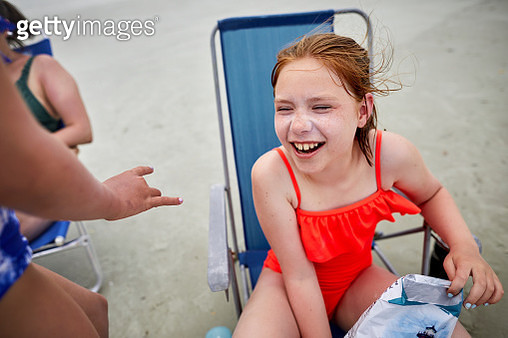 Happy girl sitting in deck chair on the beach - gettyimageskorea
