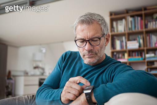 Man at home sitting on couch looking at watch - gettyimageskorea
