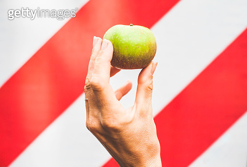 A woman's hand holds a green apple against a red and white diagonally striped background. - gettyimageskorea