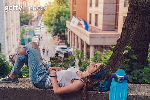 Teenage girl lying on back and listening to the music - gettyimageskorea