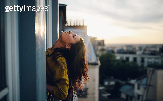Young woman relaxing on the balcony of her Parisian apartment - gettyimageskorea
