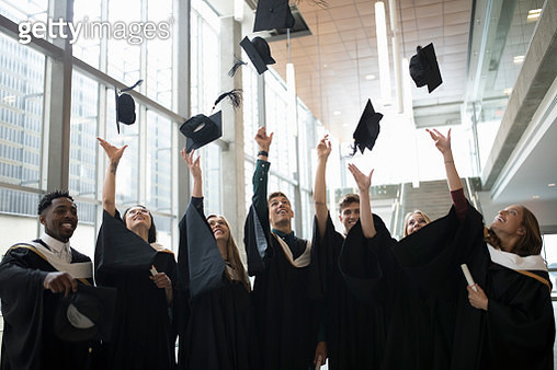 College student graduates throwing caps overhead - gettyimageskorea
