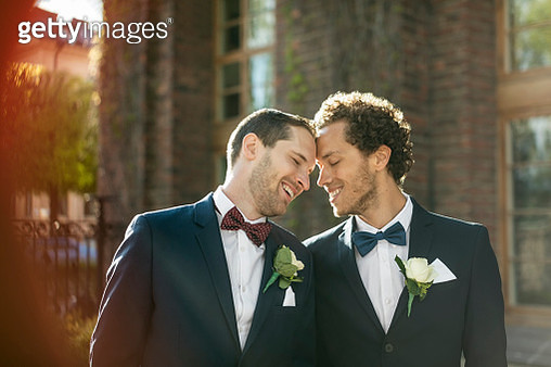 Happy newlywed gay couple standing outdoors - gettyimageskorea