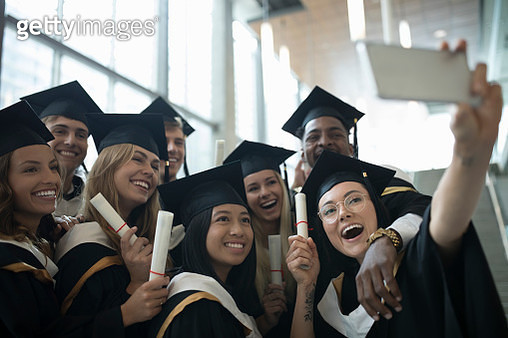 College student graduate friends in caps and gowns taking selfie with camera phone - gettyimageskorea