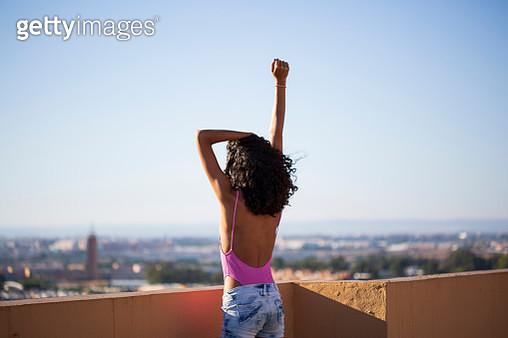 Portrait of teenage girl, raising arm, rear view - gettyimageskorea