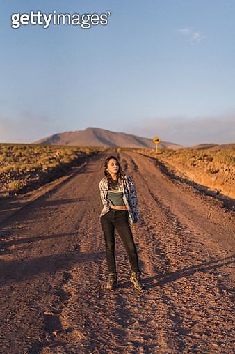 Young Caucasian woman walking on road in Atacama desert in Chile at sunset - gettyimageskorea