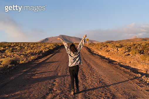 Young Caucasian woman dancing on road in Atacama desert in Chile at sunset - gettyimageskorea