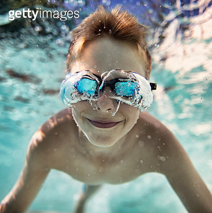 Portrait of smiling little boy enjoying underwater swim in the pool towards the camera. Funny bubble formed additional cool glasses around the boy's swimming goggles. Nikon D850 - gettyimageskorea