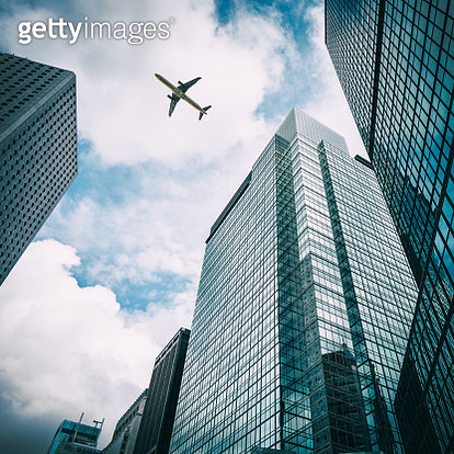 commercial airplane flying over modern office buildings - gettyimageskorea