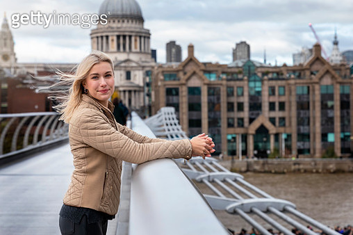 Portrait Of Smiling Woman Standing On Bridge Over River Against Buildings - gettyimageskorea