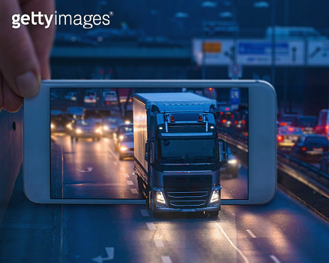 Mobile Phone displaying a truck driving through the phone - gettyimageskorea