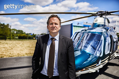 Businessman standing beside helicopter on airfield - gettyimageskorea