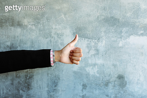 Cropped Hand Of Woman Gesturing Thumbs Up Sign Against Wall - gettyimageskorea