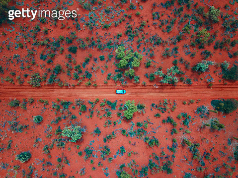 An Aerial shot of a car driving on the red centre roads in the Australian Outback - gettyimageskorea