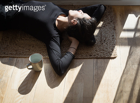 High Angle View Of Woman Lying On Floor At Home - gettyimageskorea