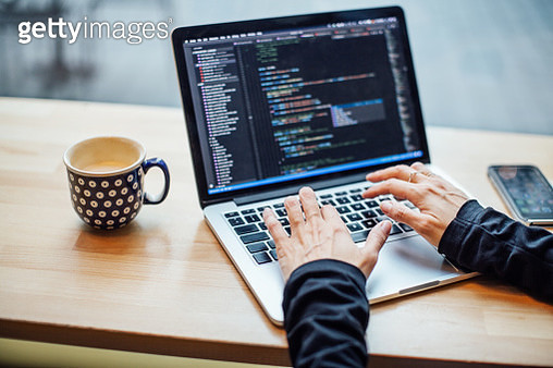 Close up of female hands working on laptop at cafe table with cup of coffee on the side. Woman busy working on her laptop at coffee shop. - gettyimageskorea