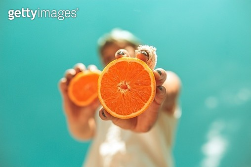 Low Angle View Of Woman Holding Orange Slices While Standing Against Blue Sky - gettyimageskorea