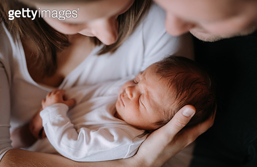 A view from directly above of young woman and man looking at their new baby boy or girl with love. - gettyimageskorea