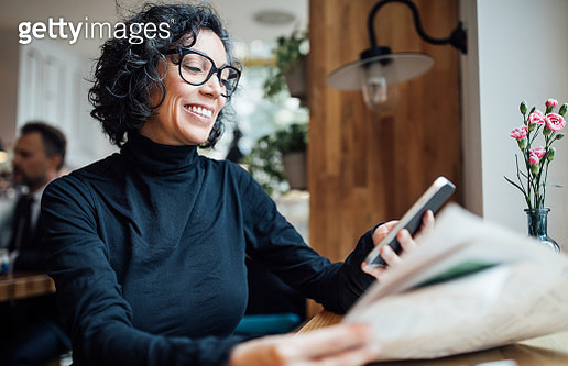 Mature woman using phone at cafe - gettyimageskorea
