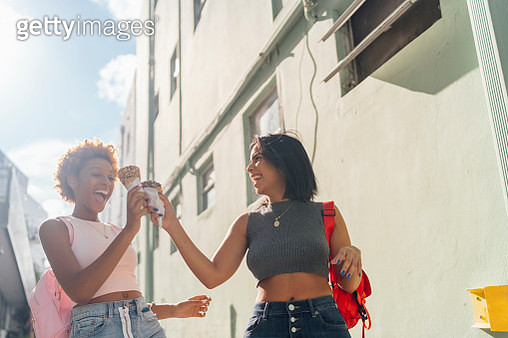 USA, Florida, Miami Beach, two happy female friends with ice cream cones in the city - gettyimageskorea