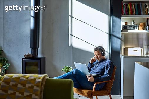 Mature man listening to music on laptop - gettyimageskorea