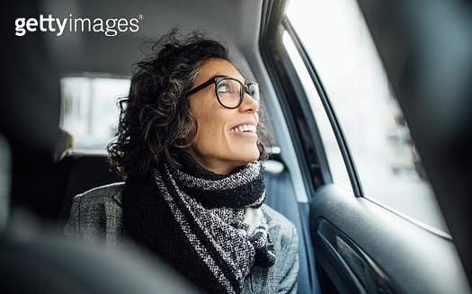 Mature woman sitting in backseat of a car looking out the window and smiling. Mid adult female traveling by a car. - gettyimageskorea