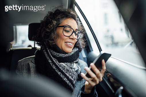 Mature businesswoman using phone while traveling by a taxi - gettyimageskorea