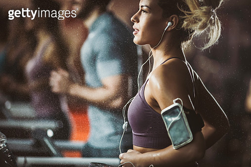 Young female athlete running on treadmill in a gym and listening music over mobile phone. - gettyimageskorea