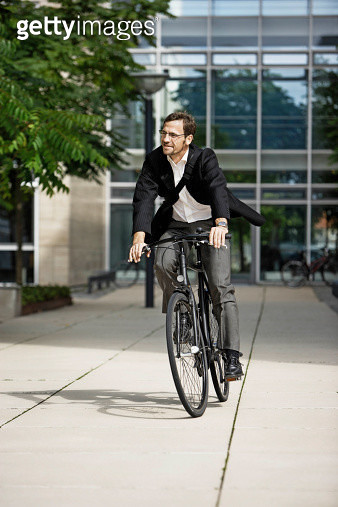 Man leaving the office on bicycle - gettyimageskorea