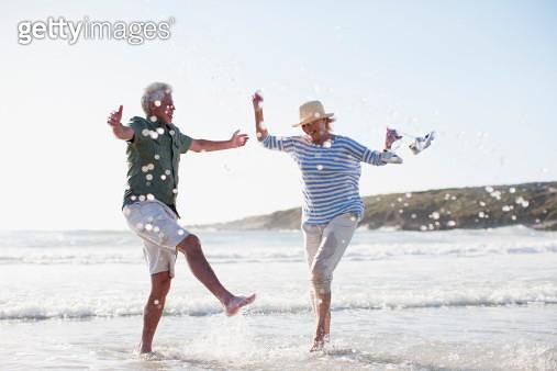 Senior couple splashing in ocean - gettyimageskorea