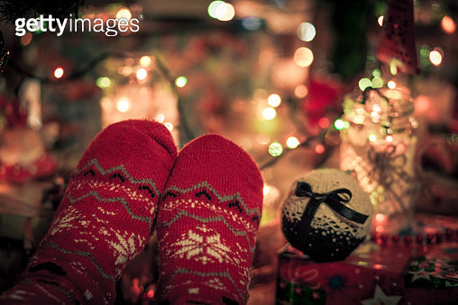 Close up of Christmas feet beneath the tree - gettyimageskorea