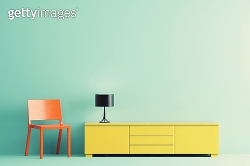 Empty Chair By Electric Lamp And Cabinet Against Colored Background - gettyimageskorea