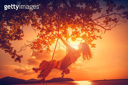 Woman at sunset swing - gettyimageskorea