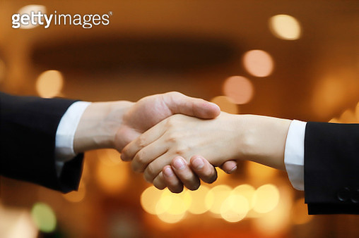 Business people shaking hands at night - gettyimageskorea