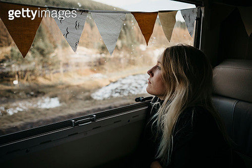 Pensive young woman looking out of car window - gettyimageskorea