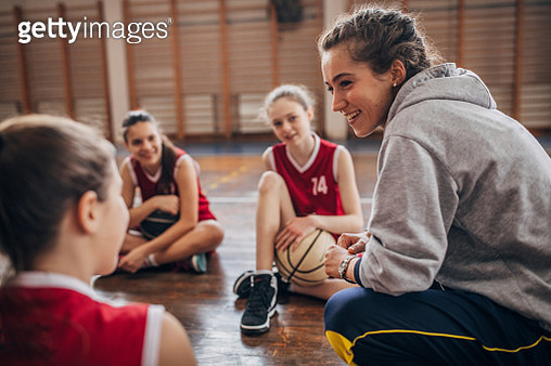 Female coach standing with basketball team on basketball court - gettyimageskorea