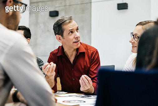 A caucasian man is speaking in a business meeting surrounded by colleagues listening to him. He uses his hands and seems convinced and focused. - gettyimageskorea