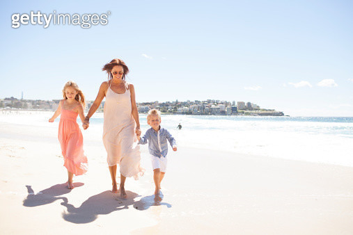 Mother and children holding hands along beach - gettyimageskorea