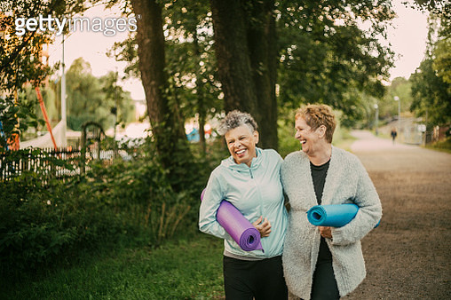 Smiling female friends holding exercise mat while walking on footpath - gettyimageskorea