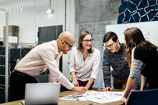 A team of four business people is standing in front a desk in a bright office room. They ambitiously point at documents while smiling and looking at the charts and notes. - gettyimageskorea