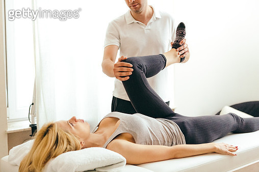 Unrecognizable physiotherapist examining leg injury on a woman lying down. - gettyimageskorea