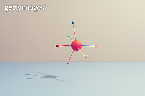 Conceptual still life with colored sticks attached to a sphere, symbolizing teamwork - gettyimageskorea