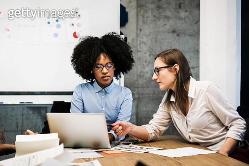A black and a caucasian young woman are sitting in a business meeting in a modern office.They discuss something over papers and a laptop while one of them is pointing at the computer screen. Both are wearing glasses and pie charts are visible in the backg - gettyimageskorea