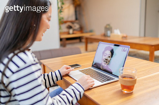Young woman keeping in touch with her loved ones while staying at home to prevent to spread of coronavirus - gettyimageskorea